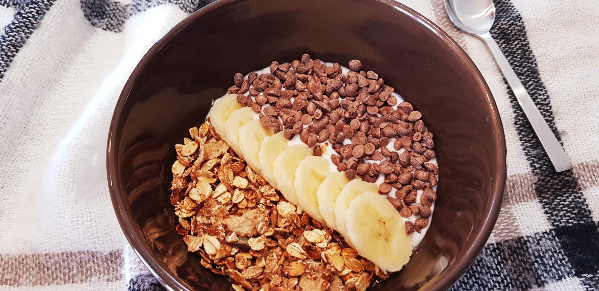 Yaourt nature, muesli, banane, et pépites de chocolat